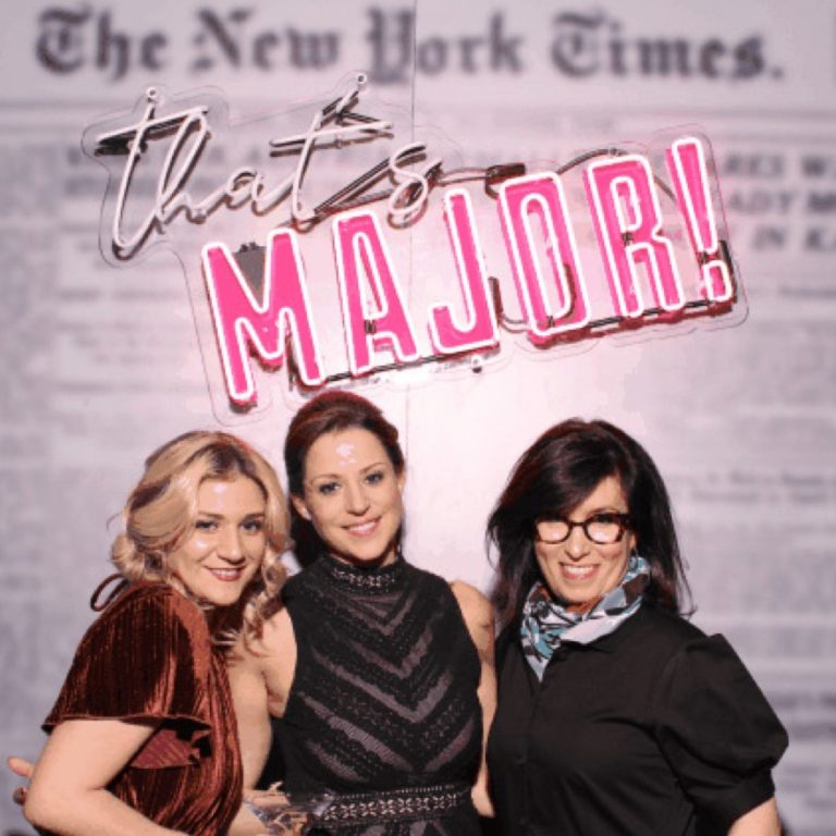 "Three women posing in front of ""That's Major"" sign"